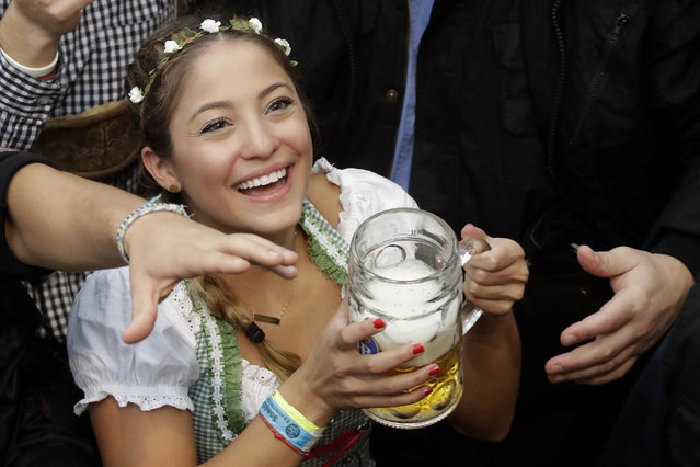 A young woman smiles with a beer during the opening of the 183rd Oktoberfest beer festival in Munich, southern Germany, Saturday, September 17, 2016. (Photo by Matthias Schrader/AP Photo)