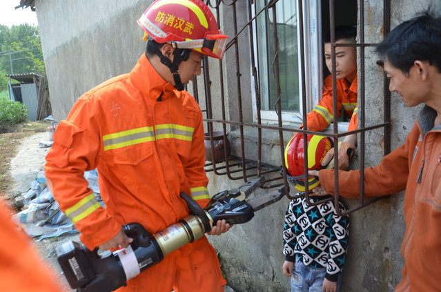 Firemen rescue a boy whose head is stuck between protective bars outside a window in Wuhan, Hubei Province, China, April 11, 2016. (Photo by Reuters/China Stringer Network)