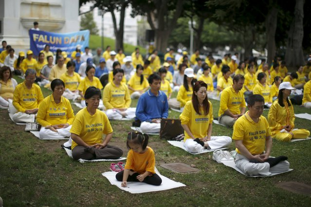 People practice Falun Dafa, or Falun Gong, meditation and exercises before a protest march against the Chinese government, outside City Hall in Los Angeles, California October 15, 2015. (Photo by Lucy Nicholson/Reuters)
