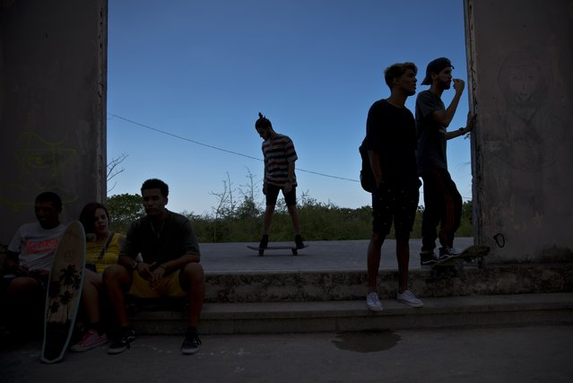 In this January 11, 2018 photo, a skater rolls by as others rest inside an abandoned gym that was converted into a recreational space for skateboarders, the day of its inauguration inside the Educational complex Ciudad Libertad, a former military barracks that the late Fidel Castro turned into a school complex after the revolution, as the sun sets in Havana, Cuba. Skateboarding apparently began with a handful of people in the 1980s and there are now hundreds of enthusiasts. (Photo by Ramon Espinosa/AP Photo)