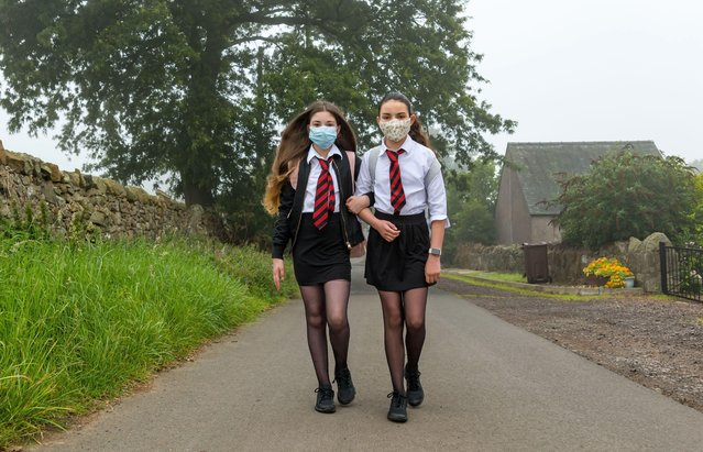 Twins Louisa and Imogen, who turned 12 years old two days ago, set off from their home on a murky morning for their first day of secondary school at North Berwick High as S1 pupils in Camptoun, Scotland on August 13, 2020. They missed out on the normal Induction Days in P7 due to the Covid-19 pandemic lockdown. (Photo by Sally Anderson News/Alamy Stock Photo)