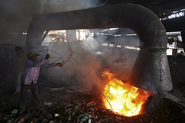 A worker throws a broken iron chair into a furnace for recycling at an iron and steel factory on the outskirts of Jammu February 1, 2013. (Photo by Mukesh Gupta/Reuters)
