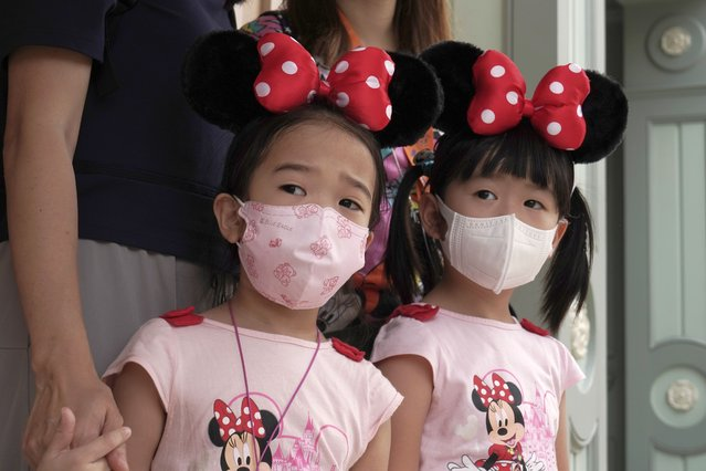 Young visitors wearing face masks look at the iconic cartoon characters Goofy and Pluto at the Hong Kong Disneyland, Friday, September 25, 2020. Hong Kong Disneyland reopened its doors to visitors after closed temporarily due to the coronavirus outbreak. (Photo by Kin Cheung/AP Photo)