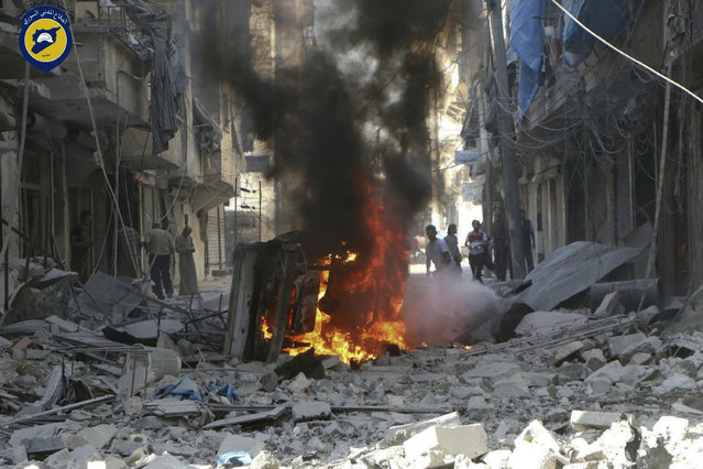 In this photo provided by the Syrian Civil Defense group known as the White Helmets, Syrians inspect damaged buildings after airstrikes by government helicopters on the rebel-held Aleppo neighborhood of Mashhad, Syria, Tuesday September 27, 2016. (Photo by Syrian Civil Defense White Helmets via AP Photo)