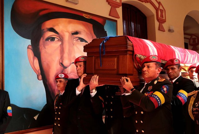 Soldiers who served with Hugo Chavez carry his coffin inside the military museum, Chavez's final resting place, where a mural of Chavez covers a wall, on March 15, 2013. (Photo by Miraflores Press Office)