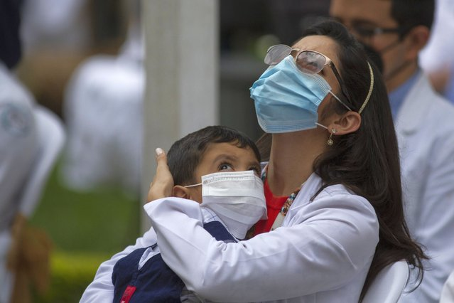 A health worker at the San Juan de Dios hospital holds a child during a minute of silence in memory of her colleagues who have fallen victim to COVID-19 in Guatemala City, Friday, October 9, 2020. (Photo by Moises Castillo/AP Photo)