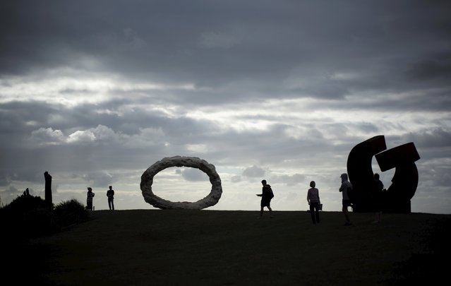 Visitors to the 19th annual Sculptures by the Sea exhibition are silhouetted against a stormy sky in Sydney, October 23, 2015. (Photo by Jason Reed/Reuters)