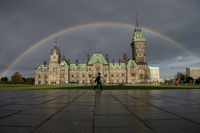 A woman walks on Parliament Hill as a rainbow arches over the East Block on Tuesday, October 7, 2014. (Photo by Justin Tang/AP Photo/The Canadian Press)