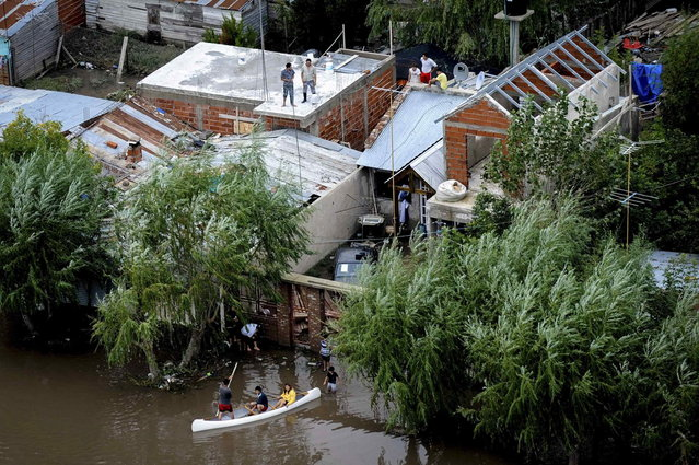 Residents stand on the roof of their homes while others paddle through a flooded street after heavy rains flooded a large part of the city, in La Plata April 3, 2013. At least 46 people were killed in Argentina on Wednesday after a torrential downpour battered the eastern city of La Plata and forced some 2,200 people to flee their homes in search of dry ground. (Photo by Reuters/Infobae.com)