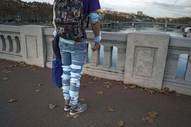 """A man wearing face masks on his legs stands on a bridge in the center of Lyon, central France, Monday, November 16, 2020. France's health minister says the country is """"progressively getting back in control"""" of its resurgent coronavirus epidemic but warns that it will quickly flare again if people start ignoring lockdown rules. (Photo by Laurent Cipriani/AP Photo)"""