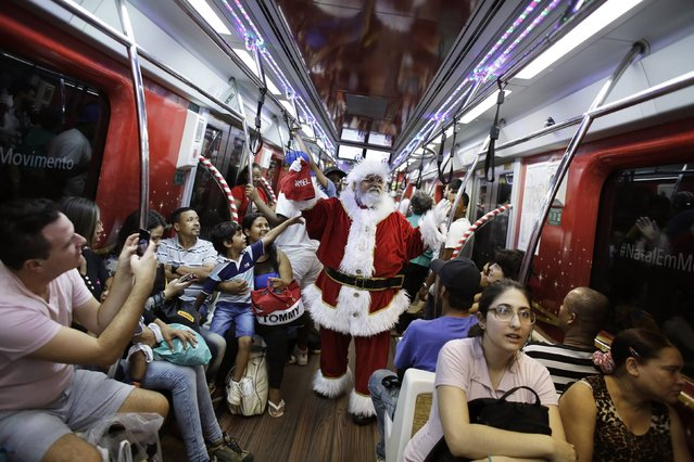A man, dressed as Santa Claus, rides a subway train as part of a promotional event by a bank in Sao Paulo December 12, 2014. (Photo by Nacho Doce/Reuters)