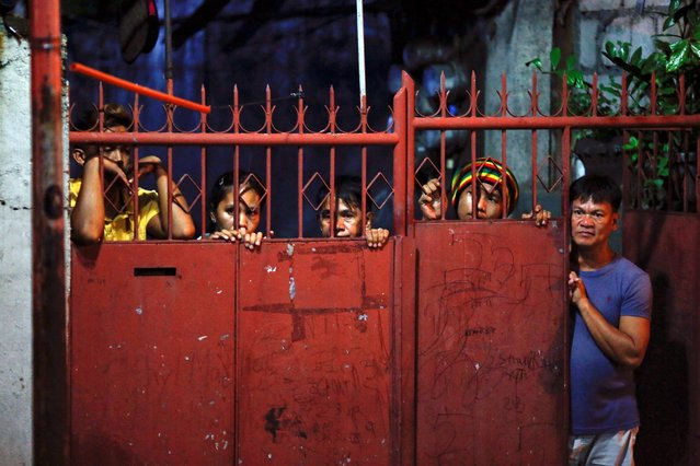 Residents look from behind a gate as police investigate a murder scene in Caloocan City, Metro Manila, Philippines early October 14, 2016. (Photo by Damir Sagolj/Reuters)