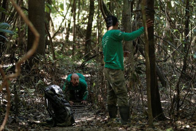 Researcher Diogo Maia Grabin (L) and his assistant Railgler dos Santos from the Mamiraua Institute install camera traps at the Mamiraua Sustainable Development Reserve in Uarini, Amazonas state, Brazil, February 9, 2018. (Photo by Bruno Kelly/Reuters)