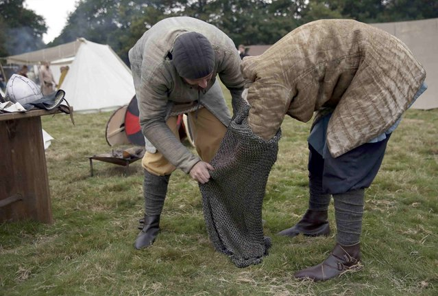 Re-enactors dress before a re-enactment of the Battle of Hastings, commemorating the 950th anniversary of the battle, in Battle, Britain October 15, 2016. (Photo by Neil Hall/Reuters)