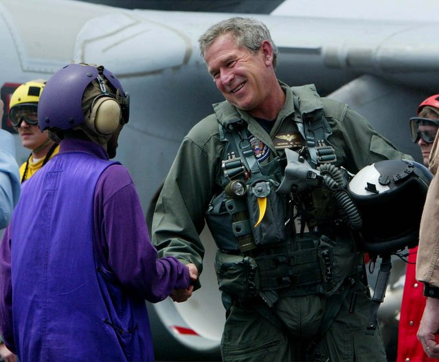 President Bush greets an unidentified sailor after landing in a small jet on the USS Abraham Lincoln off the California coast Thursday, May 1, 2003. Bush will declare that major combat in Iraq is finished during a speech aboard the carrier tonight as the Lincoln steams toward San Diego following a record 10-month deployment. (Photo by Pablo Martinez Monsivais/AP Photo)