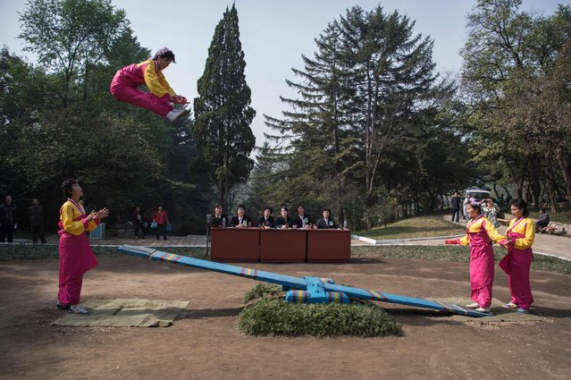 In a photo taken on October 15, 2016 competitors take part in a see-saw event during the 13th People's Games at Moran Hill park in Pyongyang. The rules of the see-saw event require competitors to consecutively jump over two-metres high for a duration of two minutes, and with each jump landing inside a small black square at the end of the see-saw. The 13th People's Games run until October 31 and feature a number of traditional Korean games with some, such as the swing and see-saw events, dating back to the Joseon dynasty. (Photo by Kim Won-Jin/AFP Photo)