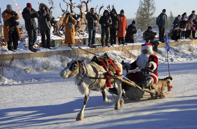 A contestant wearing a Santa Claus costume rides in a sledge pulled by a reindeer during a race on snow-covered tracks at the opening ceremony of a local winter festival in Genhe of Hulun Buir, north China's Inner Mongolia Autonomous Region, December 24, 2014. Christmas is not a traditional festival in officially atheist China but is growing in popularity, especially in more metropolitan areas where young people go out to celebrate, give gifts and decorate their homes. (Photo by Reuters/Stringer)