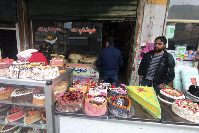 New Year cakes are displayed outside a shop in Sheikh Maksoud neighbourhood of Aleppo December 31, 2014. (Photo by Abdalrhman Ismail/Reuters)
