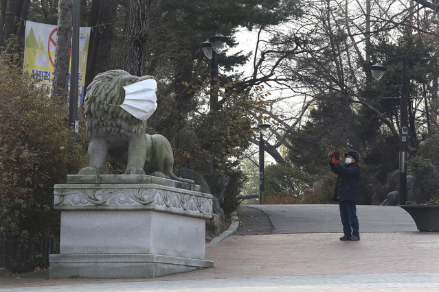 A woman wearing a face mask as a precaution against the coronavirus takes a picture of a lion statue with a face mask at a park in Seoul, South Korea, Friday, December 11, 2020. South Korea is expanding the use of rapid tests and deploying hundreds of police officers and soldiers to help with contact tracing as it deals with its worst surge of coronavirus cases since the early days of the pandemic. (Photo by Ahn Young-joon/AP Photo)