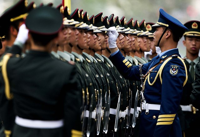 Chinese military officers use a piece of rope to line up honor guards as they prepare for a welcome ceremony for Greece's Prime Minister Antonis Samaras at the Great Hall of the People in Beijing, on May 16, 2013. (Photo by Andy Wong/Associated Press)