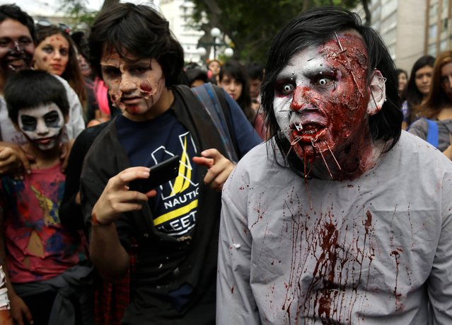 People dressed as zombies participate in the Peru Zombie Walk in Lima, Peru, Sunday, December 28, 2014. Organizers asked participants to bring diapers, pajamas, toys and other items to donate to a foster home for poor children in Lima. (Photo by Martin Mejia/AP Photo)