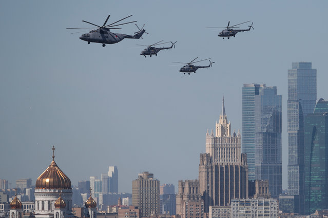 A Russian Mi-26 heavy transport helicopter and Mi-8 military helicopters fly in formation over the Christ the Saviour Cathedral and the Foreign Ministry headquarters during the Victory Day parade in Moscow, Russia on May 09, 2018. (Photo by Andrey Volkov/Reuters)