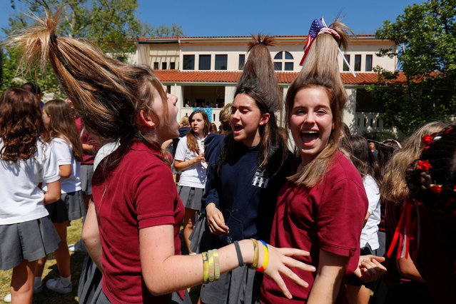 """Students wear their hair up like hats at Meghan Markle's former Los Angeles high school as they stage a """"Here's to Meghan!"""" celebration ahead of her marriage to Prince Harry, as they celebrate at Immaculate Heart High School in Los Angeles, California, U.S., May 15, 2018. (Photo by Mike Blake/Reuters)"""