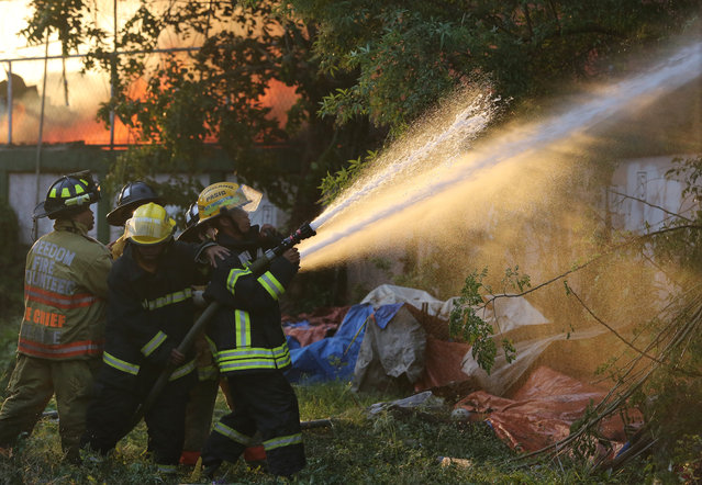 Filipino firemen train their hoses during a fire at a residential area in Mandaluyong, east of Manila, Philippines on Wednesday, November 25, 2015. Mandaluyong City Fire Marshall Nahum Tarroza said about 1,000 homes were gutted during the fire. The cause of the fire is still being investigated. (Photo by Aaron Favila/AP Photo)