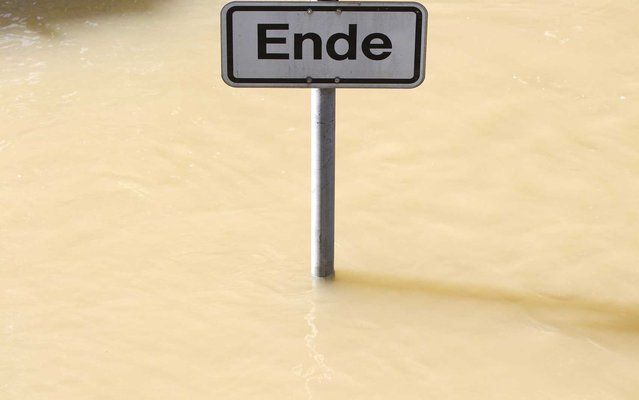 "Road sign with the word ""End"" is seen on a flooded road in Passau, Germany, on June 7, 2013. (Photo by Michaela Rehle/Reuters)"
