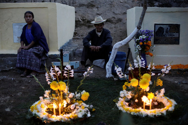 Residents sit next to the decorated tombs of their loved one during the commemoration of All Saints Day at a cemetery in Sacatepequez, Guatemala, November 1, 2016. (Photo by Luis Echeverria/Reuters)
