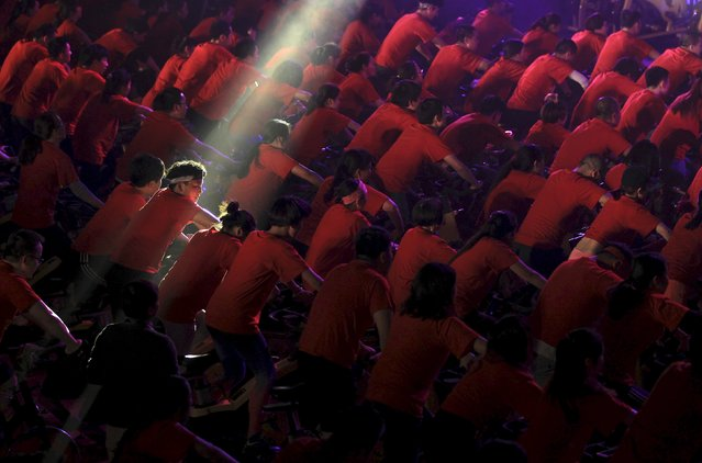 A participant is seen under a beam of light as hundreds of people ride indoor bicycles during a campaign to promote body-building exercises, at a gymnasium in Kunming, Yunnan province, China, December 1, 2015. (Photo by Wong Campion/Reuters)