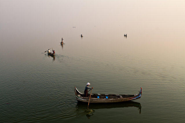 """Fishing in the sky"". Every morning at Dawn, thousands of fishing boats cross the Taungthaman lake, in the surroundings of Mandalay, Myanmar. At this time of the day, It is nearly impossible to distinguish the surface of the lake from the sky. (Photo and caption by Sophie Revillard/National Geographic Traveler Photo Contest)"
