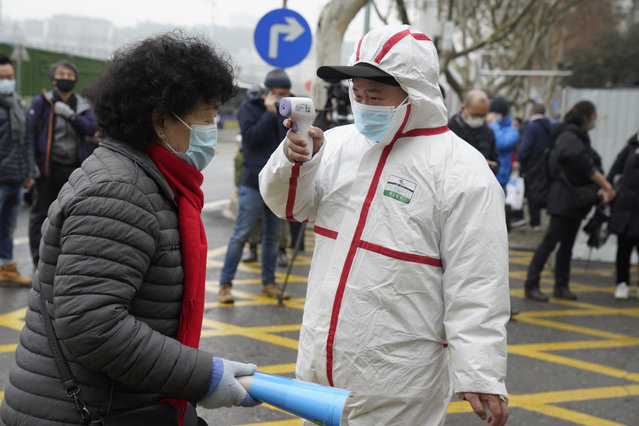 A worker in protective overalls takes the temperature of a woman entering the Hubei Center for Disease Control and Prevention as the World Health Organization team makes a field visit in Wuhan in central China's Hubei province on Monday, February 1, 2021. A World Health Organization team investigating the origins of the coronavirus pandemic visited a provincial disease control center that had an early hand in managing the outbreak. (Photo by Ng Han Guan/AP Photo)