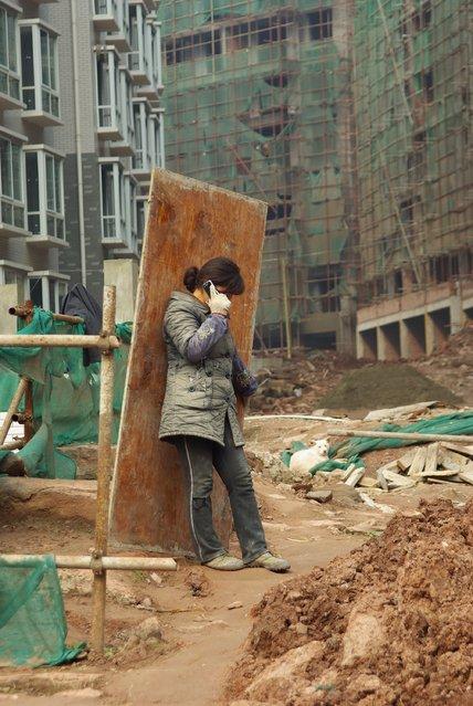 """""""《无安全帽的女工》 (Have no the woman worker of safety helmet)"""". 2012-2-15, in Sichuan, China province support a woman worker of a workplace of the Yue county of Anne in sun City didn't wear whole hatses. (Photo and caption by Xianlie Hong/National Geographic Traveler Photo Contest)"""