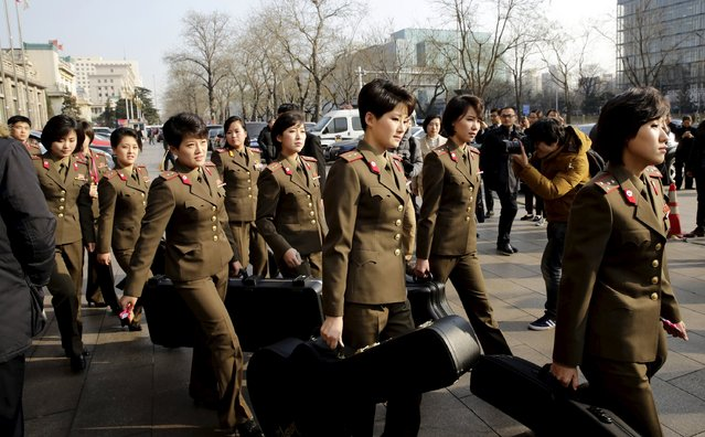Members of the Moranbong Band from North Korea carry their instruments as they leave a hotel in central Beijing, China, December 11, 2015. (Photo by Reuters/Stringer)