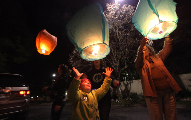 People light up and release lanterns outside Nelson Mandela's house in Johannesburg, South Africa, Monday July 1, 2013. Mandela remains in critical condition in a hospital in Pretoria. (Photo by Tsvangirayi Mukwazhi/AP Photo)
