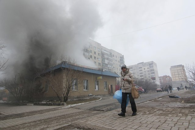 A woman resident passes by a burning house in Mariupol, Ukraine, Saturday, January 24, 2015. (Photo by Sergey Vaganov/AP Photo)