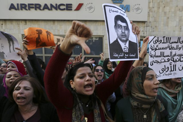 """Protesters chant anti-government slogans while holding a poster of Egyptian Interior Minister Mohamed Ibrahim with the words, """"Wanted, the killer of Shaimaa al-Sabbagh"""" during a protest by women at the same location in central Cairo where activist Shaimaa Sabbagh was killed during a protest on Saturday, January 29, 2015, one day before the anniversary of the popular uprising that ousted autocrat Hosni Mubarak in 2011. (Photo by Mohamed Abd El Ghany/Reuters)"""