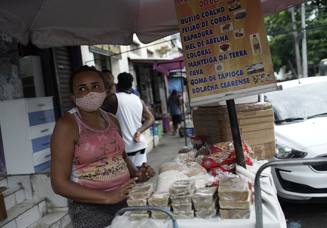 A street vendor wearing a mask amid COVID-19 sells cheese, beans, and sweets in Rio de Janeiro, Brazil, Friday, October 9, 2020. Many people in Brazil are struggling to cope with less pandemic aid from the government and jumping food prices, with millions expected to slip back into poverty. (Photo by Silvia Izquierdo/AP Photo)