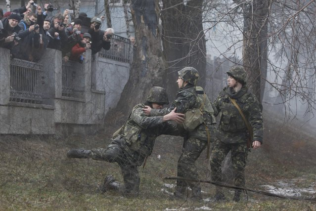 """A Ukrainian serviceman guarding Ukraine's Defence Ministry is helped up by his colleagues after failing to arrest a member of the """"Aydar"""" battalion who entered the ministry compound, during a protest against the disbanding of the battalion in Kiev February 2, 2015. (Photo by Valentyn Ogirenko/Reuters)"""