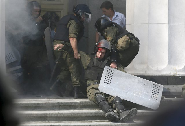 An injured national guard officer is carried away by comrades outside the parliament building in Kiev, Ukraine, August 31, 2015. (Photo by Valentyn Ogirenko/Reuters)