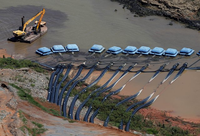 A machine from SABESP (L), a Brazilian enterprise of Sao Paulo state that provides water and sewage services to residential, commercial and industrial areas, works next to pumps from the Jaguari dam station, which provides water to the SABESP systems, during a drought in Braganca Paulista, Sao Paulo state February 12, 2015. (Photo by Paulo Whitaker/Reuters)