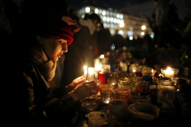 A woman lights a candle as people gather on the Place de la Republique square to pay tribute to the victims of last year's shooting at the French satirical newspaper Charlie Hebdo, in Paris, France, January 7, 2016. France this week commemorates the victims of last year's Islamist militant attacks on satirical weekly Charlie Hebdo and a Jewish supermarket with eulogies, memorial plaques and another cartoon lampooning religion. (Photo by Stephane Mahe/Reuters)