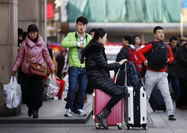 A woman sits on her luggage case at a railway station in Beijing February 16, 2015. (Photo by Kim Kyung-Hoon/Reuters)