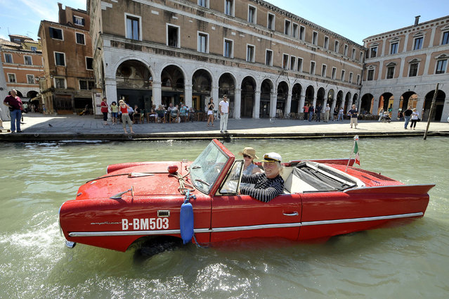 Bernd Weise, of the Amphicar Club Berlin, pilots his 1961 Amphicar down the Grand Canal in Venice May 28, 2009. The German-built amphibious car, which uses a Triumph Herald engine, is capable of over 110 kph (70mph) by road and 8 knots on water. Its driver a needs regular driving licence and a boat licence. (Photo by Michele Crosera/Reuters)