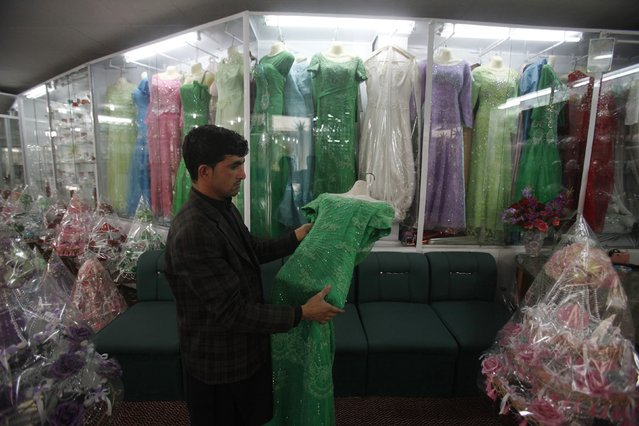 An Afghan refugee man, who have a residency card which will expire on December 2015, puts women dresses on display at his shop on the outskirts of Peshawar February 18, 2015. (Photo by Fayaz Aziz/Reuters)