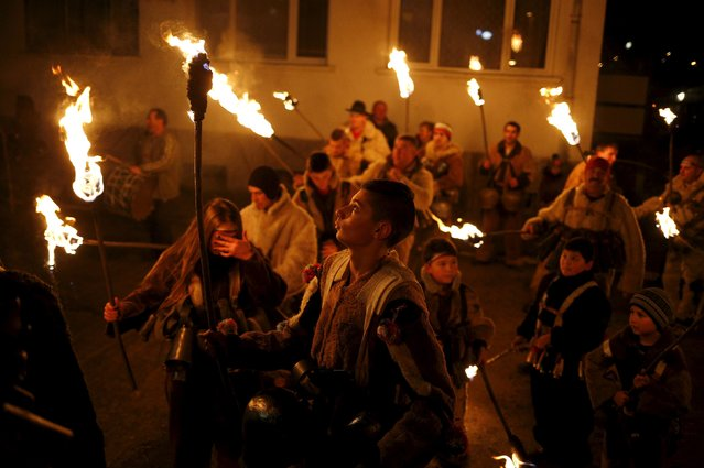 "People dressed in costumes made of animal fur, called ""kuker"", carry torches during a festival in the village of Vitanovtsi, Bulgaria January 13, 2016. Each winter, thousands of people in many Bulgarian towns and villages take part in traditional celebrations for good health and fertility, wearing masks and costumes made of animal fur. (Photo by Stoyan Nenov/Reuters)"