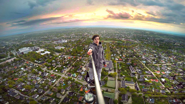 Ervin Punkar using a selfie stick to take a photo from the very top of the 600ft TV tower in Tartu, Estonia. (Photo by Ervin Punkar/Caters News Agency)
