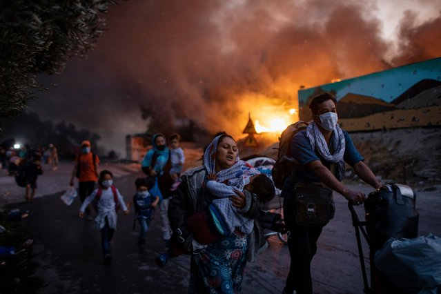 Single News Third Prize. Refugees and migrants carrying their belongings flee a fire burning at the Moria camp on the north-eastern Aegean island of Lesbos, Greece. (Photo by Petros Giannakouris/AP Photo/Istanbul Photo Awards 2021)