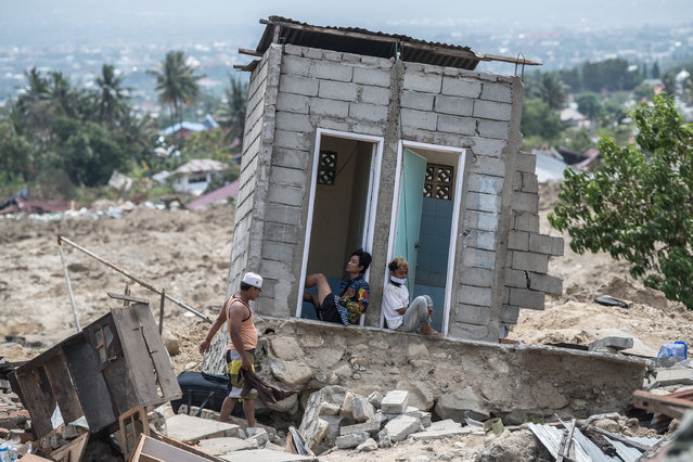 People rest in what was a toilet block in an area that was completely destroyed by an earthquake, on October 04, 2018 in Palu, Indonesia. The death toll from last weeks earthquake and tsunami has risen to at least 1,400, with time running out to rescue survivors six days after the disaster struck, and food, water, fuel and medicine were still slow to reach the hardest-hit areas outside the city of Palu on Sulawesi island. A tsunami triggered by a magnitude 7.5 earthquake slammed into Indonesia's coastline on the island of Sulawesi which destroyed or damaged over 66,000 homes as tensions are running high and Indonesia's military said it will shoot looters after desperate survivors emptied shops of food and water. (Photo by Carl Court/Getty Images)